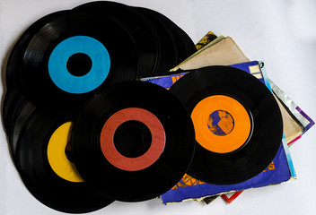 Old beat up 45s and their paper sleeves.