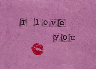 Words I love you and kiss stamped on pink paper