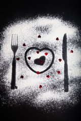 Silhouettes of fork, knife and hearts on the flour on a black ba