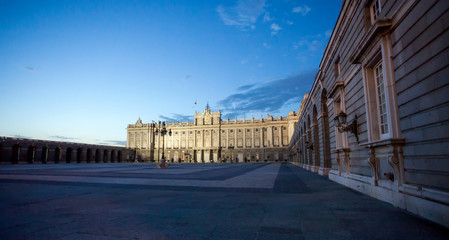 Royal palace with tourists illuminated on spring night in Madrid