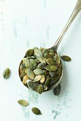 Green pumpkin seeds on an old spoon