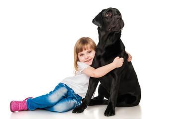 Beautiful girl hugging a black Labrador
