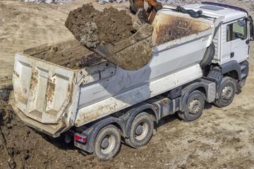 excavator bucket full of dirt and truck