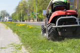 Road landscaper cutting grass along city street