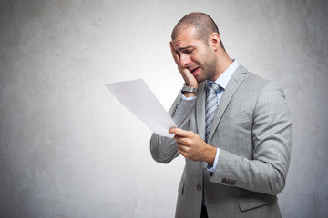 Sad man reading a document