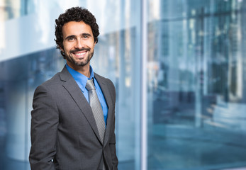 Smiling businessman in front of a glass wall
