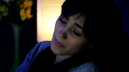 Sad desperate woman in bed crying alone closeup