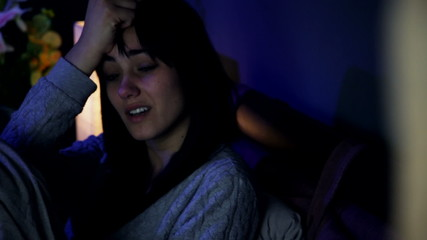 Sad desperate woman in bed crying alone