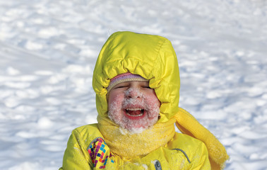 child to lie in the snow and laughs
