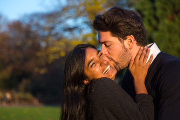 Couple hugging and kissing outside in park