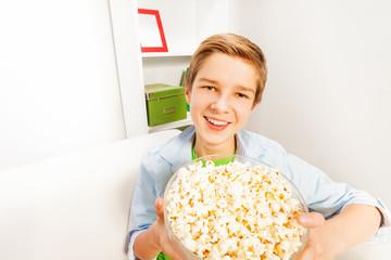 Happy boy with big popcorn bowl on white sofa