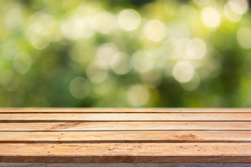 Empty wooden deck table on bokeh natural background