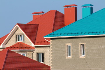 Cottages with red and blue roofs against a blue sky