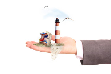 Leuchtturm und Strandkorb auf einer Hand