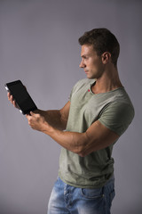 Attractive young man holding ebook reader or tablet PC