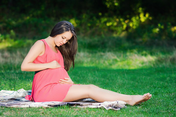 Young pregnant woman relaxing in park outdoors