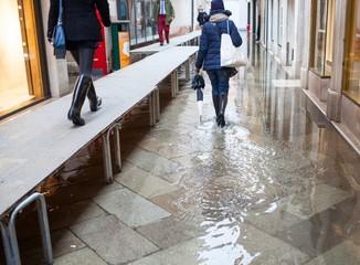 Persone passeggiano in una strada di Venezia con l'acqua alta