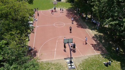 Aerial view on group of people playing basketball in local park.