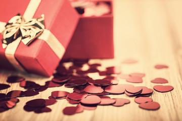 Red hearts confetti on wooden background in retro color