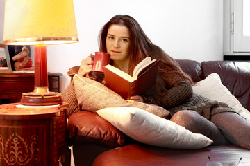girl at home over sofa with book and cup of tea