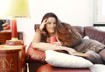 smiling girl in relax with tea mug and a book