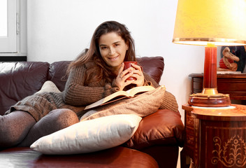 smiling woman in relax with tea mug over sofa