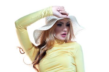 Beautiful girl in a hat enjoying the sun on the beach