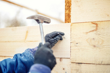 worker or handyman hammering nails in timber