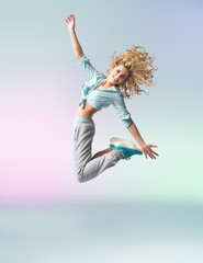 Curly-haired athlete woman jumping and dancing