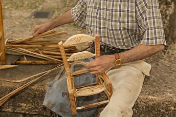 Hombre haciendo una silla de madera y enea.