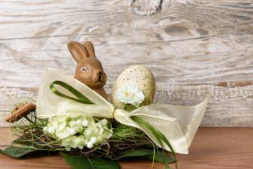 Osterhase mit Osterei im Nest vor Holz Hintergrund als Ostergru