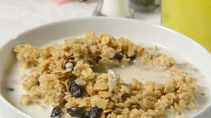 A spoonful of granola with nuts and raisins