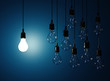 Hanging light bulbs with glowing one isolated on dark blue backg