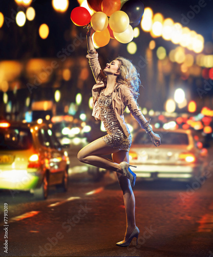 Fun-loving girl holding a bunch of balloons