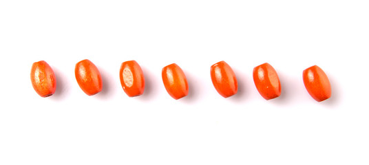Orange colored wooden oval shaped beads over white background