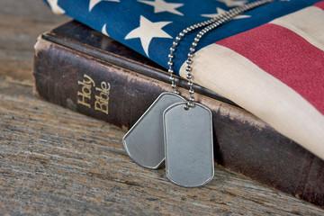 military dog tags on Bible and flag