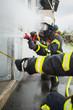 Leinwanddruck Bild - Feuerwehrmänner an einem brennenden Gebäude