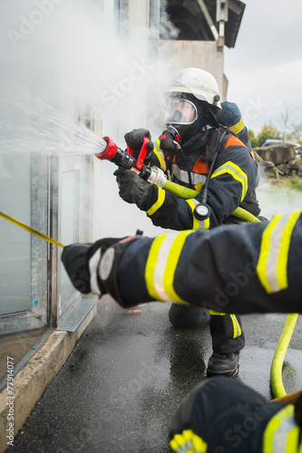 Leinwanddruck Bild Feuerwehrmänner an einem brennenden Gebäude
