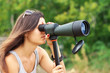 Leinwandbild Motiv Positive girl who is watching in spotting scope.