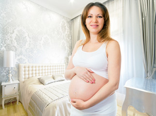 A cute pregnant woman in the bedroom