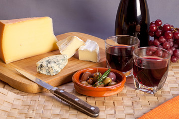 Glasses of red wine and mediterranean appetizers.