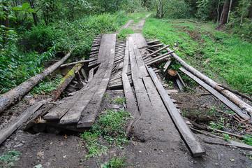 Dirty broken wooden bridge in forest