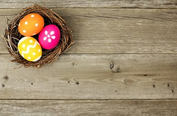 Easter eggs in a nest over an old wood background
