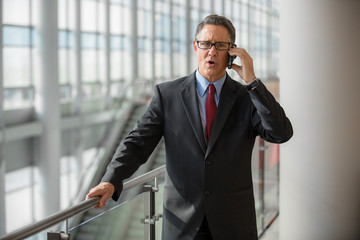 Businessman getting bad news on the phone at the airport