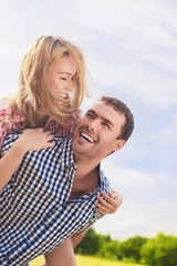 Portrait of Happy and Cheerful Young Caucasian Couple Piggybacki