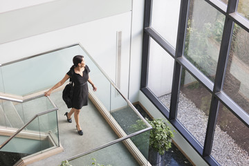Hispanic businesswoman on stairs in office building
