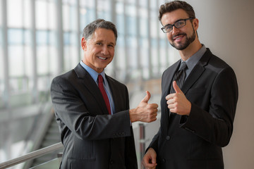 Two businessmen giving a thumbs-up