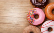 Donuts on wooden background - 77917603