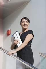 Businesswoman holding folders on stairs of office building