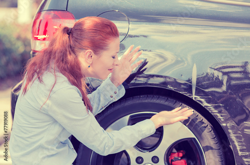 Frustrated woman checking pointing at car scratches dents - 77919088